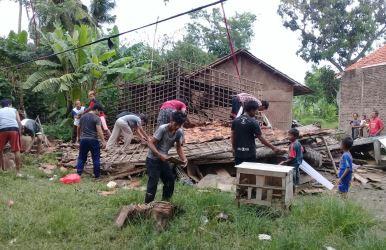 Warga setempat saat membersihkan puing bangunan rumah milik Samsudin yang ambruk pada Sabtu (20/01) kemarin.
